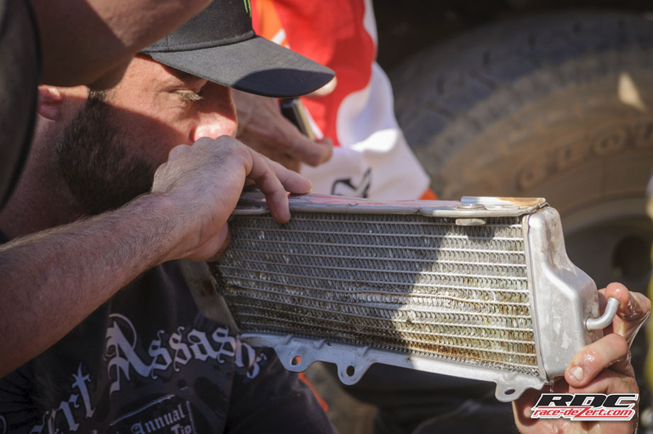 """A man of many talents, Bryan Bergey plays a ceremonial tune on Destry Abbott's busted radiator before deploying the 'ol """"black-pepper-in-the-radiator-trick"""". Works every time."""