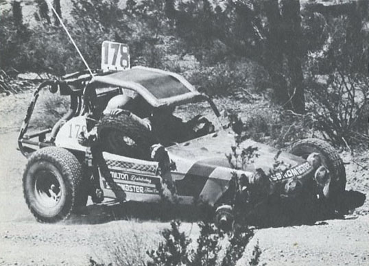 IS THIS TRIP REALLY NECESSARY?—Willis Hamilton, somewhere in Baja, continuing to motor on despite losing front spindle. Buggy will drive on three wheels, but not at competition speed. (Photo by Bob Neth)