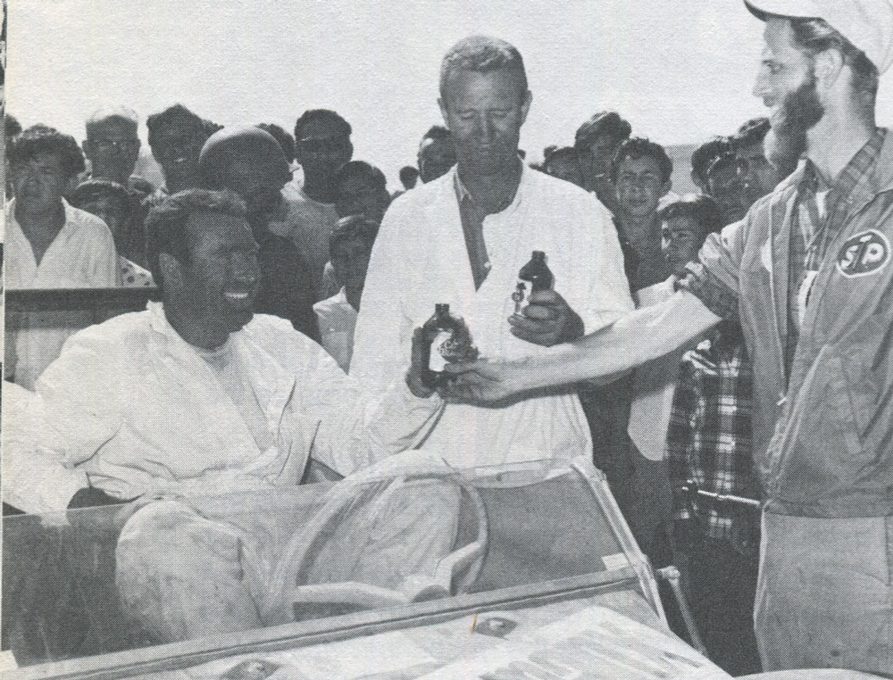 Assist. Steward Lou Gross hands that first beer to 1967 MEXICAN 1000 winners Vic Wilson (l.) and Ted Mangels. (Image Intl. Photo)
